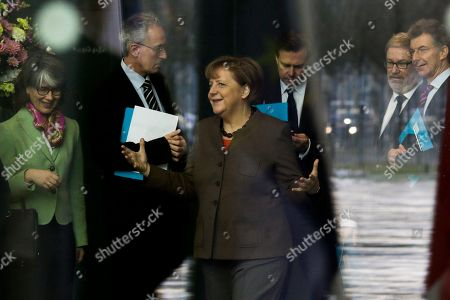 Through a window with reflections, German Chancellor Angela Merkel, center, talks to staff as she is on her way to welcome the Prime Minister of Slovenia Miroslav Cerar for talks at the chancellery in Berlin, Germany