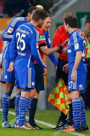 Referee Florian Meyer argues to Schalke's Sascha Riether and his teammates during the German Bundesliga soccer match between FC Augsburg and FC Schalke 04 at the WWK Arena stadium in Augsburg, Germany