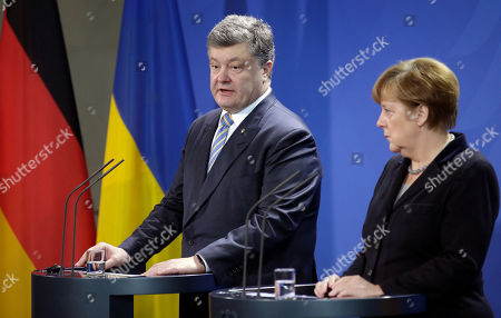 German Chancellor Angela Merkel, right, and the President of Ukraine, Petro Poroschenko, left, address the media during a joint statement as part of a meeting at the chancellery in Berlin, Germany