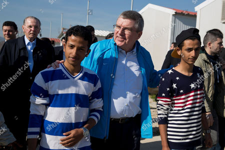 Thomas Bach, Jacques Rogge IOC President Thomas Bach, center, walks with two young refugees with former IOC President Jacques Rogge in the background, during their visit at a refugee camp in Athens on Thursday, Jan, 28, 2016. Bach says the torch relay for this year's Olympics in Rio de Janeiro will include a stop at a refugee camp in Athens. He also promised to build sporting facilities on the island of Lesbos that has been hard hit by the migrant crisis