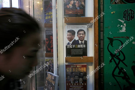 A woman walks past a book featuring a photo of Chinese President Xi Jinping, left, and former Politburo member and Chongqing city party leader Bo Xilai on the cover, at the entrance of the closed Causeway Bay Bookstore which is known for gossipy titles about Chinese political scandals and other sensitive issues that are popular with visiting tourists from the mainland in Hong Kong . Hong Kong pro-democracy lawmakers say they'll press the government for answers after a fifth employee of a publisher specializing in books critical of China's ruling communists went missing
