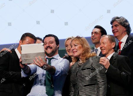 Italy's Northern League leader Matteo Salvini, third from left, takes group photos with, from left, Japan's Tomio Okamura, Austria's Heinz-Christian Strache (hidden), Salvini, French National Front president Marine Le Pen, Britain's Janice Atkinson, Belgium's Tom Van Grieken, Poland's Michal Marusik and Dutch Marcel De Graaf, at the end of the Europe of Nations and Freedom movement meeting in Milan, Italy