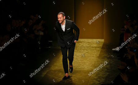 Italian Fashion designer Massimiliano Giornetti acknowledges the applause of the audience at the end of the Salvatore Ferragamo men's Fall-Winter 2016-2017 show, part of the Milan Fashion Week, unveiled in Milan, Italy