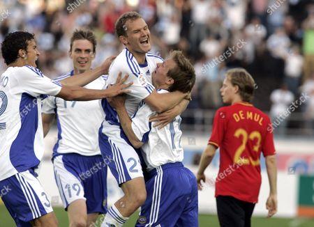Finland's Roman Eremenko (L), Toni Kallio, Jonatan Johansson and Joonas Kolkka celebrate after Jonatan Johansson's first goal while Belgium's Tom De Mul (R) walks by during the Euro 2008 Group A qualifying match.