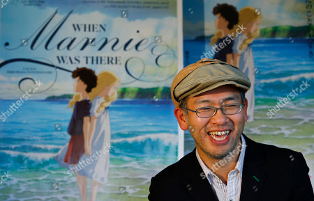 """Hiromasa Yonebayashi Japanese director Hiromasa Yonebayashi smiles about his latest film """"When Marnie Was There"""" with its poster during an interview at his office, Studio Ghibli, in suburban Tokyo. The coming-of-age story is familiar: A shy girl has problems fitting in and concocts an imaginary friend. The originality of the Oscar-nominated """"When Marnie Was There"""" comes from how its hand-drawn images express the girl's inner torment. Luscious hand-drawn animation is the trademark of Japan's renowned Studio Ghibli, where the film's director Yonebayashi worked for years"""