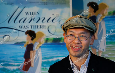 """Hiromasa Yonebayashi Japanese director Hiromasa Yonebayashi speaks about his latest film """"When Marnie Was There"""" with its poster during an interview at his office, Studio Ghibli, in suburban Tokyo. Yonebayashi says the ways his artists have carefully depicted cloudy skies and rippling waves express the soul of the main character, Anna, who nurses a scar in her heart because she is adopted. """"It's a challenge to convey internal emotions visually such as through her facial expressions and the landscape,"""" he said quietly in the interview. """"The wind is cold, but there is warmth in an embrace"""