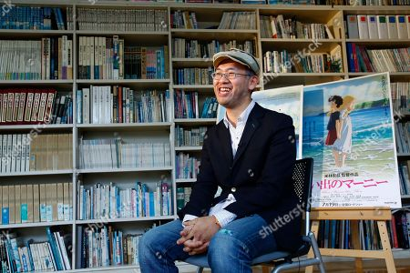 """Stock Photo of Hiromasa Yonebayashi Japanese director Hiromasa Yonebayashi smiles about his latest film """"When Marnie Was There"""" with its poster during an interview at his office, Studio Ghibli, in suburban Tokyo. The coming-of-age story is familiar: A shy girl has problems fitting in and concocts an imaginary friend. The originality of the Oscar-nominated """"When Marnie Was There"""" comes from how its hand-drawn images express the girl's inner torment. Luscious hand-drawn animation is the trademark of Japan's renowned Studio Ghibli, where the film's director Yonebayashi worked for years"""