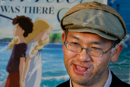 """Stock Image of Hiromasa Yonebayashi Japanese director Hiromasa Yonebayashi speaks about his latest film """"When Marnie Was There"""" with its poster during an interview at his office, Studio Ghibli, in suburban Tokyo. The coming-of-age story is familiar: A shy girl has problems fitting in and concocts an imaginary friend. The originality of the Oscar-nominated """"When Marnie Was There"""" comes from how its hand-drawn images express the girl's inner torment. Luscious hand-drawn animation is the trademark of Japan's renowned Studio Ghibli, where the film's director Yonebayashi worked for years"""