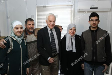 Canadian Minister of Immigration John McCallum, center, poses for a photograph with a Syrian family soon to be resettled in Canada, at the UN refugee agency building in Amman, Jordan. McCallum said the country's resettlement program for Syrian refugees could double by the end of 2016