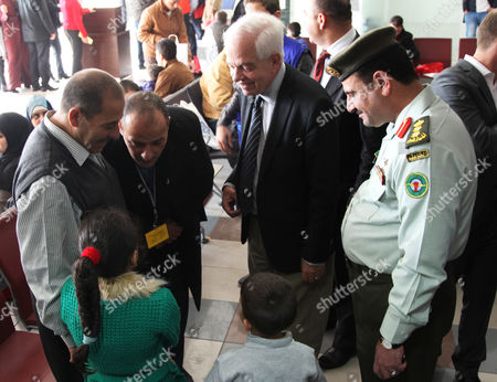 Canadian Minister of Immigration John McCallum, center, talks to a Syrian family soon to be flown from an airport in Amman, Jordan to live in Canada, . McCallum said the country's resettlement program for Syrian refugees could double by the end of 2016