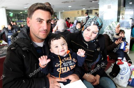 Radi poses for a photo with his son and wife, who names are omitted for security reasons, while waiting in an airport in Amman, Jordan, to board a plane to Canada where they will be resettled, . Canadian Minister of Immigration John McCallum said the country's resettlement program for Syrian refugees could double by the end of 2016