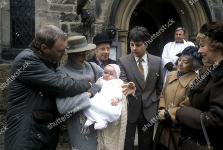 'Emmerdale'  TV -  1983 - The Christening of Sam Skilbeck Matt Skilbeck [Frederick Pyne], Dolly Skilbeck [Jean Rogers], Sam Skilbeck [Benjamin Whitehead?], Sam Pearson [Toke Townly], Joe Sugden [Frazer Hines], Aunt Jessie [Kathleen Helme], and Annie Sugden [Sheila Mercier].  Rev Donald Hinton [Hugh Manning] watches what's going on.