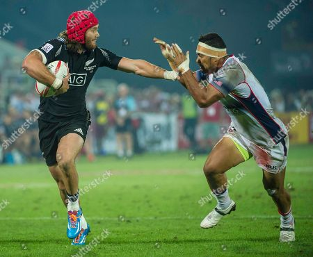 Gillies Kaka of New Zealand hands off Folau Niua of the US in the Pool C match during the first day of the Sevens World Series rugby tournament in Dubai, United Arab Emirates