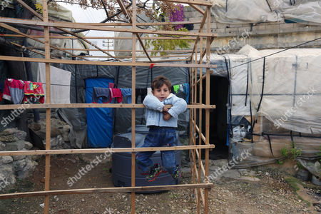 A Syrian refugee boy plays outside his family tent, before the visit of Canadian Minister of Immigration John McCallum to a Syrian refugee camp in the southern town of Ghaziyeh, near the port city of Sidon, Lebanon