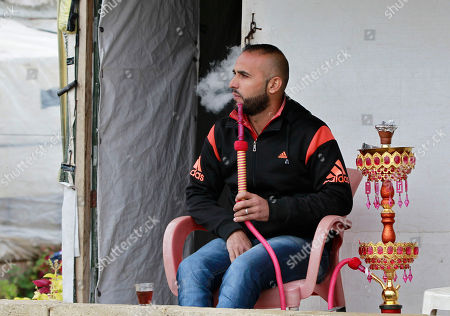 Syrian refugee Mohanna Hameed, 30, who fled his home in Homs in Syria, smokes a water pipe in front of his tent, during the visit of Canadian Minister of Immigration John McCallum to a Syrian refugee camp in the southern town of Ghaziyeh, near the port city of Sidon, Lebanon
