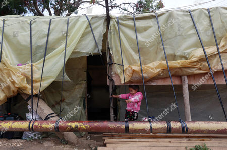 A Syrian refugee stands outside her family tent, during the visit of Canadian Minister of Immigration John McCallum to a camp in the southern town of Ghaziyeh, near the port city of Sidon, Lebanon