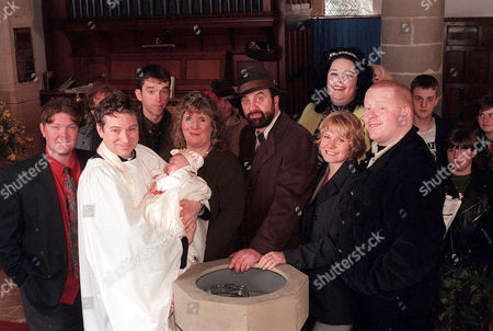 'Emmerdale'  TV - 1999 - The day for  Belle Dingle's (EMILY MATHERS) Christening has finally arrived. Pictured: L-R (back row) Paddy Kirk (DOMINIC BRUNT), Marlon Dingle (MARK CHARNOCK), Mandy Dingle (LISA RILEY). (Front row) Reverend Ashley Thomas (JOHN MIDDLETON), Lisa Dingle (JANE COX), Zak Dingle (STEVE HALLIWELL), Rachel Hughes (GLENDA McKAY), Butch Dingle (PAUL LOUGHRAN).