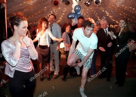 'Emmerdale'  TV - 1999 - Marlon Dingle (MARK CHARNOCK) performs a striptease for Lyn Hutchinson (SALLY WALSH) in an attempt to win back her affections. Back row left to right:  Tricia [Sheree Murphy], Jack (CLIVE HORNBY), Sarah (ALYSON SPIRO), Graham (KEVIN PALLISTER), Rachel (GLENDA McKAY), Pollard (CHRIS CHITTELL) and Stella (STEPHANIE SCHONFIELD).