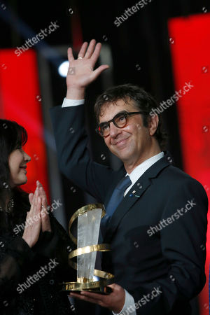 Canadian director Atom Egoyan waves and holds an award for the Tribute to Canadian Cinema as Canadian actress Carole Laure, left, applauds during a ceremony at the 15th Marrakech International Film Festival in Marrakech, Morocco, . The festival runs from Dec. 4-12
