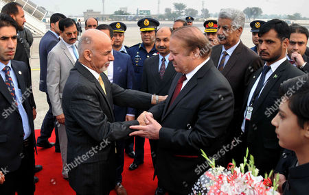 """Pakistani Prime Minister Nawaz Sharif, center right, greets Afghan President Ashraf Ghani, center left, upon his arrival at Nur Khan airbase in Rawalpindi, Pakistan, . Ghani and Sharif jointly opened the one-day """"Heart of Asia"""" ministerial conference in Pakistani capital Islamabad to seek joint efforts to bring peace to war-torn Afghanistan"""