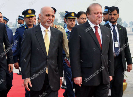 """Afghan President Ashraf Ghani, left, walks with Pakistani Prime Minister Nawaz Sharif upon his arrival at Nur Khan airbase in Rawalpindi, Pakistan, . Ghani and Sharif jointly opened the one-day """"Heart of Asia"""" ministerial conference in Pakistani capital Islamabad to seek joint efforts to bring peace to war-torn Afghanistan"""