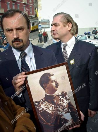 In this Feb.13 2003, file picture an unidentified man holds a photograph of Romania's King Carol II as Romania's Prince Paul, right, walks past outside a church in Lisbon, Portugal, where the king was buried. Prosecutors have detained Romania's Prince Paul, in a case of alleged real estate fraud involving a top aide to a former prime minister and a newspaper editor