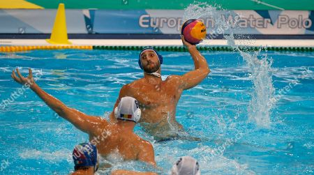 Italy's Valentino Gallo, right, prepares to throw the ball past Romania's Mihnea Chioveanu during their qualifying match at the men's European Waterpolo Championships in Belgrade, Serbia