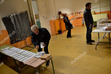 Francisco Javier Perez Francisco Javier Perez, 60 years old, collects a voting slip to vote at polling station for the national elections, in Pamplona northern Spain, . Spaniards are voting in an historic national election Sunday with the country's traditional two-parties contesting with a widely anticipated strong showings for two new parties