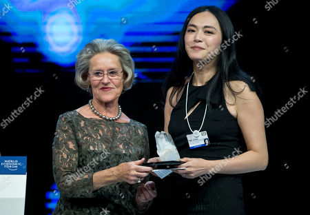 Chairperson and Co-Founder of the Schwab Foundation Hilde Schwab, left, hands over to Chinese actress Yao Chen the Crystal Awards at the World Economic Forum in Davos, Switzerland, . The world's political and business elite are being urged to do more than pay lip service to growing inequalities around the world as they head off for this week's World Economic Forum in the Swiss ski resort of Davos this week