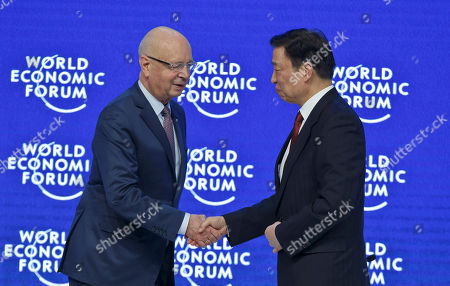 President and Founder of the World Economic Forum Klaus Schwab, left, welcomes Chinese Vice President Li Yuanchao on stage for a special session at the World Economic Forum in Davos, Switzerland, . World leaders are holding a flurry of diplomatic meetings at the World Economic Forum and worried CEOs are debating about how to deal with this year's volatile markets and low oil prices