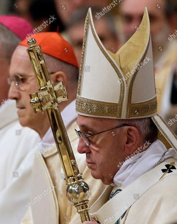 Pope Francis, left, walks with Cardinal Tarcisio Bertone as he arrives to celebrate a Mass in St. Peter's Basilica, at the Vatican, to mark Epiphany, . The Epiphany day is a joyous day for Catholics in which they recall the journey of the Three Kings, or Magi, to pay homage to Baby Jesus