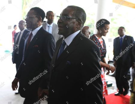 Zimbabwean President Robert Mugabe, right, holds hands with Equatorial Guinea President Teodoro Obiang Nguema Mbasago at State House in Harare, Saturday, January, 23, 2016. Mugabe,91, who was rumored to be sick and hospitalized returned from his annual vacation Friday