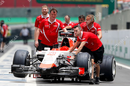 Mechanics push the car of Marussia driver Will Stevens of Britain, at the Interlagos race track in Sao Paulo, Brazil, . The Brazil Formula 1 GP will take place Sunday