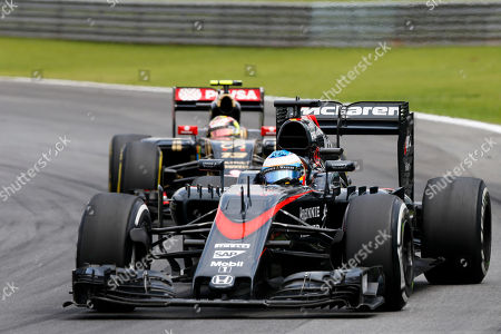 McLaren driver Fernando Alonso, of Spain, steers his car followed by Lotus driver Pastor Maldonado, of Venezuela, during the Formula One Brazilian Grand Prix at the Interlagos race track in Sao Paulo, Brazil