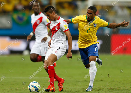 Brazil's Douglas Costa, right, and Peru's Paolo Hurtado fight for the ball during a 2018 World Cup qualifying soccer match in Salvador, Brazil