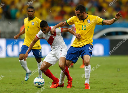 Peru's Paolo Hurtado and Brazil's Renato Augusto, right, fight for the ball during a 2018 World Cup qualifying soccer match in Salvador, Brazil
