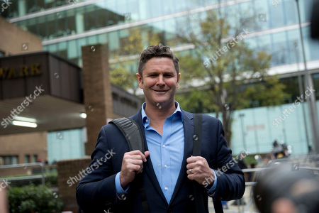 Former New Zealand cricket captain Chris Cairns stops to pose for photographers as he leaves after being found not-guilty in his perjury trial at Southwark Crown Court in London, . Cairns was cleared Monday of perjury and perverting the course of justice during a libel action about match-fixing but said he believes his career in the sport is over. The London jury cleared the retired cricketer of all charges at the end of a nine-week trial at Southwark Crown Court