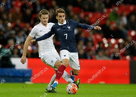 France's Antoine Griezmann, right is challenged by England's Eric Dier during the international friendly soccer match between England and France at Wembley Stadium in London, . France is playing England at Wembley on Tuesday after the countries decided the match should go ahead despite the deadly attacks in Paris last Friday night which killed scores of people