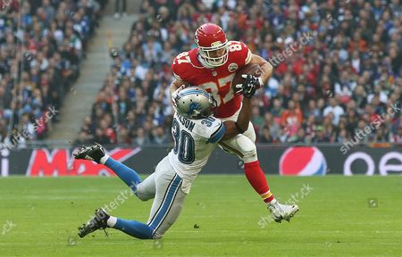 Detroit Lions defensive back Josh Wilson (30), left, tackles Kansas City Chiefs tight end Travis Kelce (87) during the NFL football game between Detroit Lions and Kansas City Chiefs Wembley Stadium in London