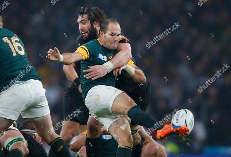 South Africa's captain Fourie Du Preez kicks the ball despite the tackle of New Zealand's Samuel Whitelock during the Rugby World Cup semifinal match between New Zealand and South Africa at Twickenham Stadium in London