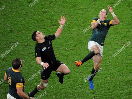 South Africa's Fourie du Preez, right, and New Zealand's Daniel Carter leap to compete for the ball as South Africa's Duane Vermeulen, left, watches during their Rugby World Cup semifinal match between South Africa and New Zealand at Twickenham Stadium, London