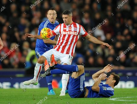 Stoke's Jonathan Walters, centre, under pressure from Chelsea's John Terry, left, and Chelsea's Nemanja Matic during the English Premier League soccer match between Stoke City and Chelsea at the Britannia Stadium, Stoke on Trent, England
