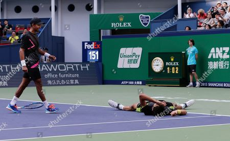 Marcelo Melo of Brazil, right, lying on the court celebrates as his partner Raven Klaasen of South Africa walks to Melo after winning their doubles final match against Simone Bolelli and Fabio Fognini of Italy in the Shanghai Masters tennis tournament at Qizhong Forest Sports City Tennis Center in Shanghai, China