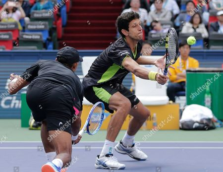 Marcelo Melo of Brazil, right, hits a return shot next to Raven Klaasen of South Africa during their doubles final match against Simone Bolelli and Fabio Fognini in the Shanghai Masters tennis tournament at Qizhong Forest Sports City Tennis Center in Shanghai, China