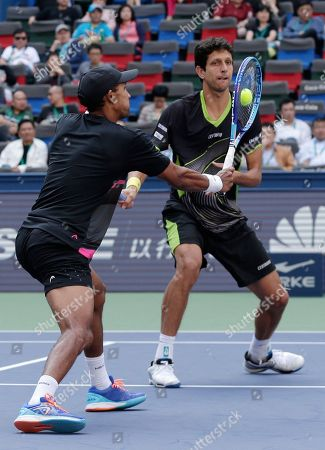 Raven Klaasen of South Africa, left, hits a return shot next to Marcelo Melo of Brazil during their doubles final match against Simone Bolelli and Fabio Fognini in the Shanghai Masters tennis tournament at Qizhong Forest Sports City Tennis Center in Shanghai, China