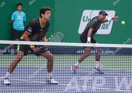 Raven Klaasen of South Africa, right, hits a return shot next to Marcelo Melo of Brazil during their doubles final match against Simone Bolelli and Fabio Fognini in the Shanghai Masters tennis tournament at Qizhong Forest Sports City Tennis Center in Shanghai, China