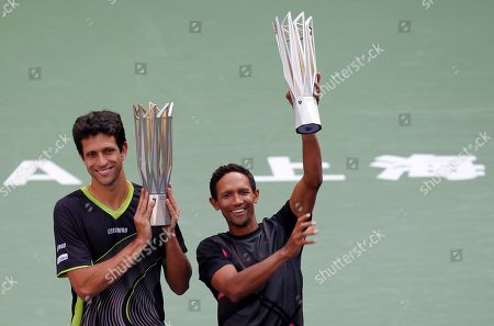 Marcelo Melo of Brazil, left, and Raven Klaasen of South Africa hold their trophies after defeating Simone Bolelli and Fabio Fognini of Italy in the doubles final match of the Shanghai Masters tennis tournament at Qizhong Forest Sports City Tennis Center in Shanghai, China