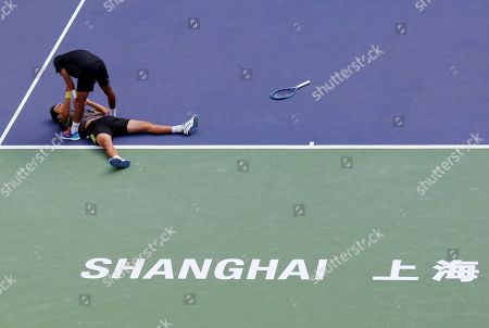 Marcelo Melo of Brazil lying on the court celebrates with Raven Klaasen of South Africa after defeating Simone Bolelli and Fabio Fognini of Italy in the doubles final match of the Shanghai Masters tennis tournament at Qizhong Forest Sports City Tennis Center in Shanghai, China