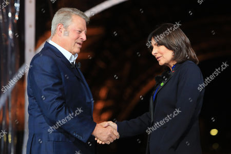Former U.S. Vice President Al Gore shakes hand with Paris' mayor Anne Hidalgo, as he hosts a 24-hour live webcast from the foot of the Eiffel Tower, in Paris, . Gore, who helped negotiate the 1997 climate treaty that failed to control global warming, will host the round-the-clock event that includes musical performances by Elton John, Duran Duran and others. Other concerts will be broadcast from locations around the globe, from Rio de Janeiro to Miami, Sydney and Cape Town