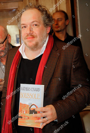 """French writer Mathias Enard, poses for photographers with his book """"Boussole"""" (Compass) after being awarded with the 2015 Goncourt literary prize, in Paris, France, . As is traditional, the Prix Goncourt was announced at the Drouant restaurant in Paris"""